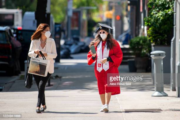 Mother wearing a mask walks with her daughter wearing a mask, cap and gown amid the coronavirus pandemic on May 14, 2020 in New York City. The New...
