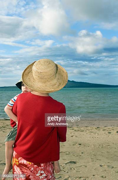 Mother wearing hat carrying daughter (2-4) on beach, rear view