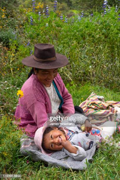 mother wearing local hat and baby cuddle and enjoy picnic in the grass, near chumbe community, lamay, sacred valley, peru (2 model releases) - james strachan stock pictures, royalty-free photos & images