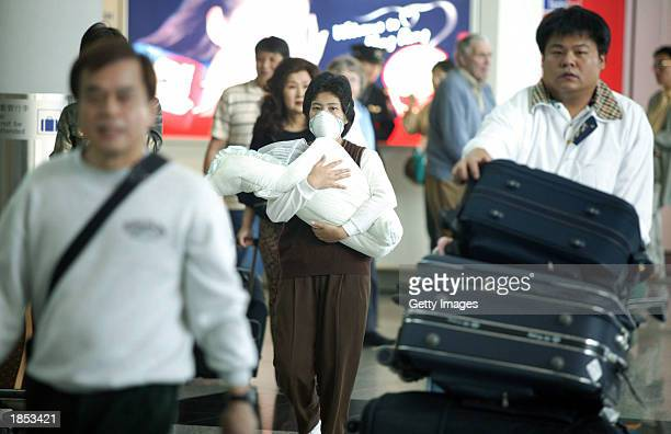 Mother wears a face mask as she carries her baby into Hong Kong's Chek lap Kok airport to protect herself from a flu-like virus that's hit the region...