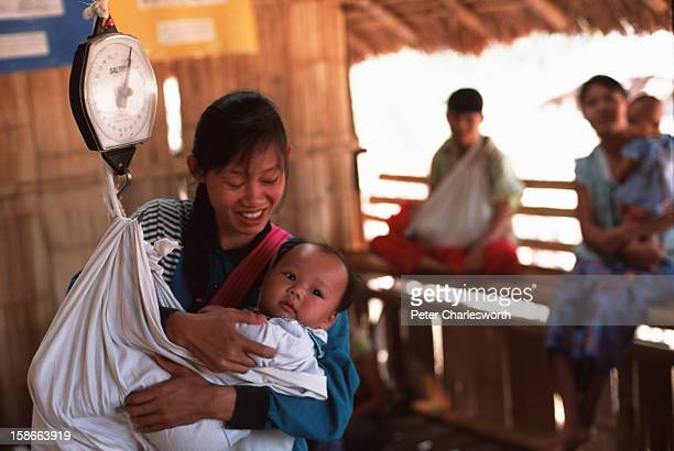 Mother weighs her child at a clinic in a Karen refugee camp north of the Thai town, Mae Sot. Checking children's weight and height is an important...