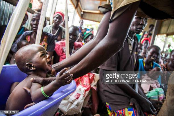 TOPSHOT A mother weights her malnourished child on May 31 in a nutrition centre run by the International Rescue Committee in Panthau Northern Bahr al...