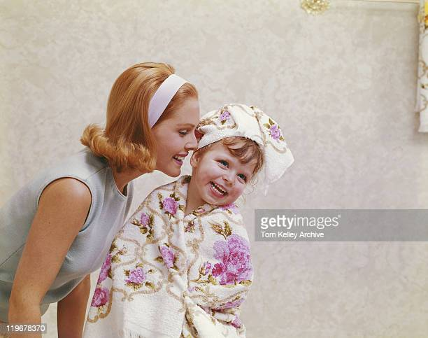 Mother whispering into daughter's ear, smiling