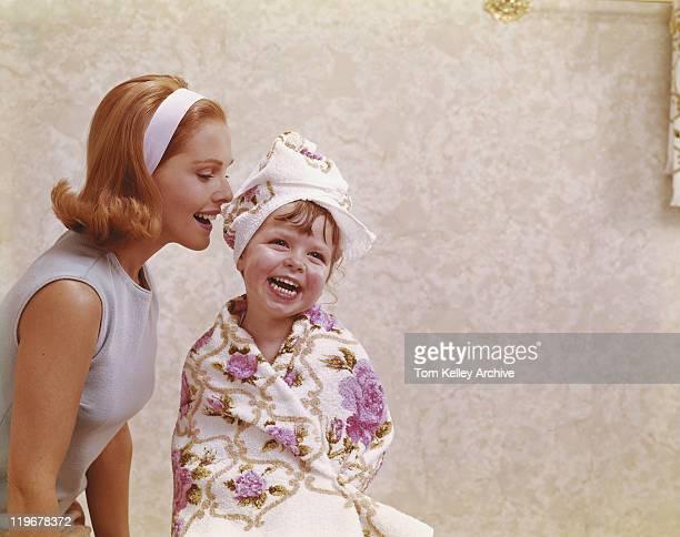 Mère Chuchoter à l'oreille de sa fille, souriant