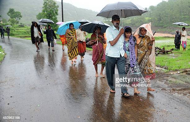 A mother who had lost her three children in a landslide is accompanied by villagers to a temporary mortuary at Malin village in Pune district of...