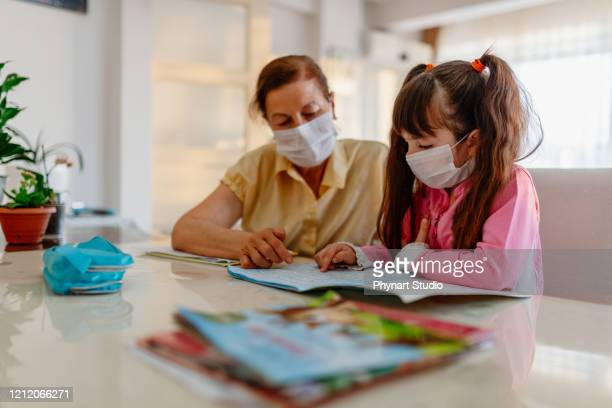 mother who teaches his daughter, who could not go to school because of the disease outbreak, at home - spelling stock pictures, royalty-free photos & images