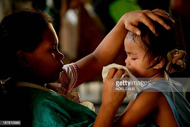 Mother wipes the face of her daughter as they wait to take a flight on a C-130 military plane out of Tacloban, Leyte province, central Philippines on...