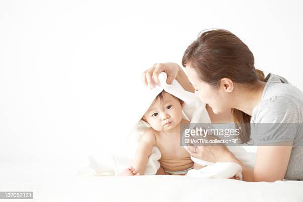Mother wiping baby with towel