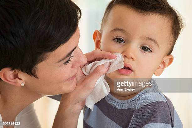 Mother wiping nose of baby son with tissue