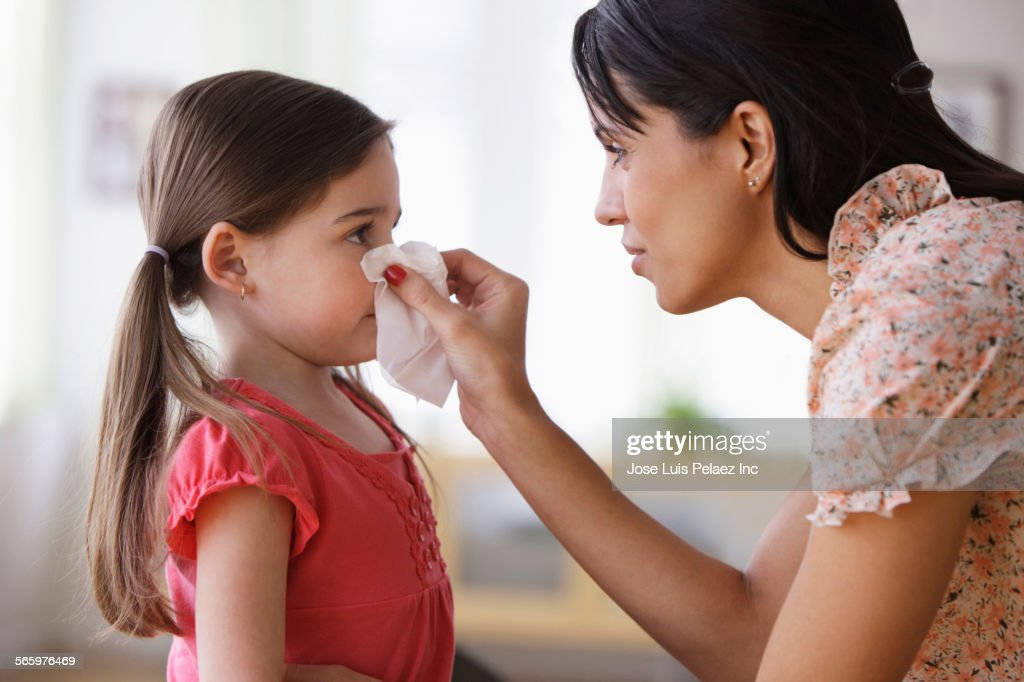 Mother wiping nose of daughter with tissue : Stock Photo