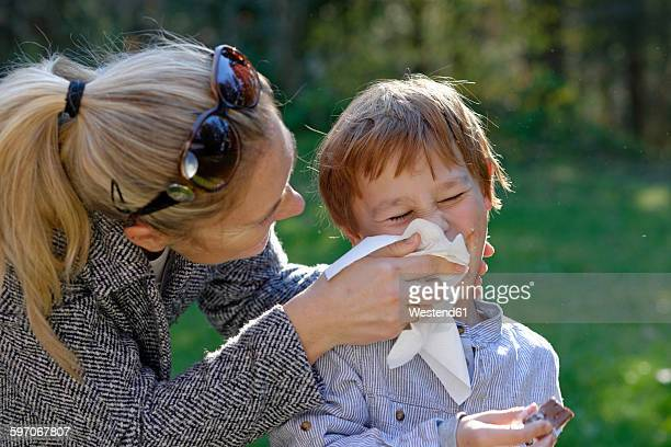 Mother wiping the face of her son