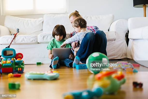 Mother with 2 kids using a digital tablet