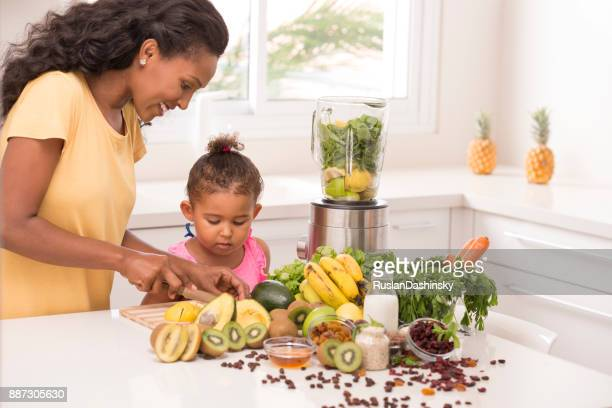 mother with 2-3 years old daughter cutting fruits in the kitchen. - mint plant family stock pictures, royalty-free photos & images