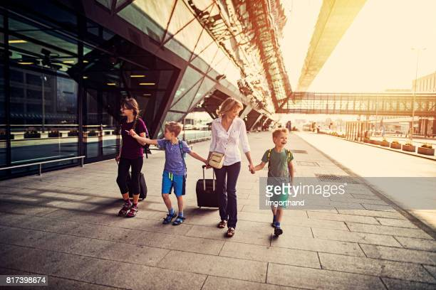 Mother with 3 kids walking at the airport