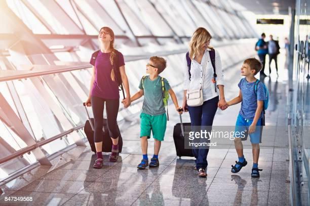 Mère de 3 enfants, marche dans le hall de l'aéroport