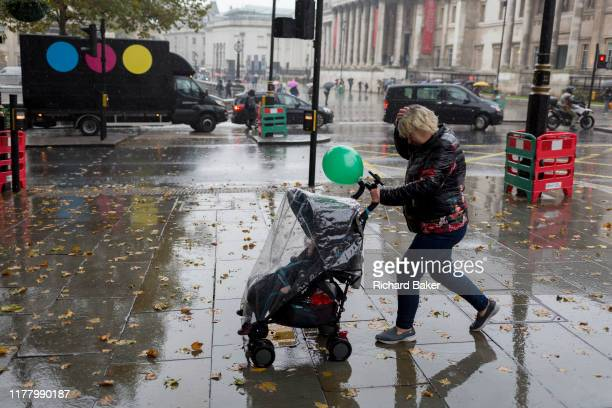 A mother with a green balloon walks past a film industry delivery van during heavy rainfall on an autumn afternoon in Trafalgar Square on 24th...