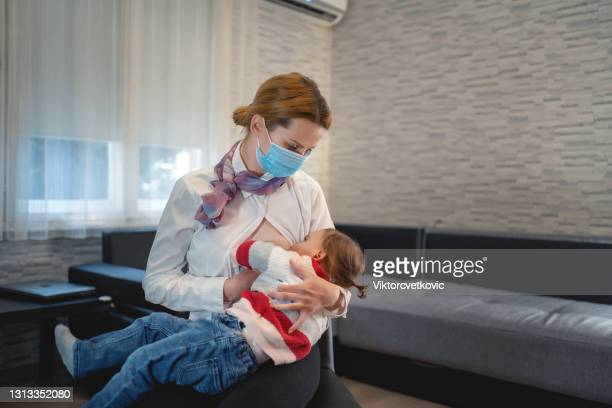 a mother with a protective mask breastfeeds her child at home in isolation - audience free event stock pictures, royalty-free photos & images