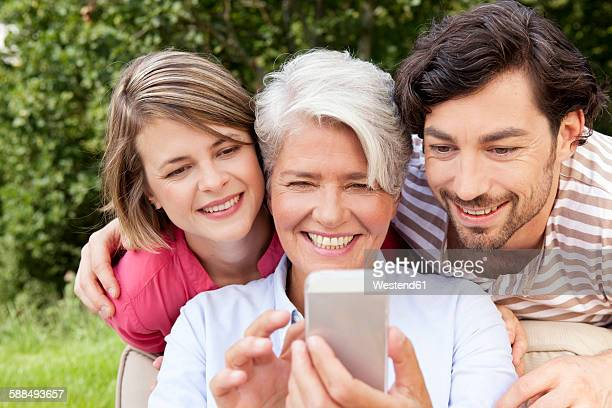 Mother with adult children looking at cell phone outdoors