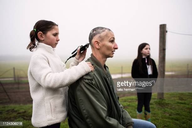 Mother with alopecia has her head shaved by her daughters