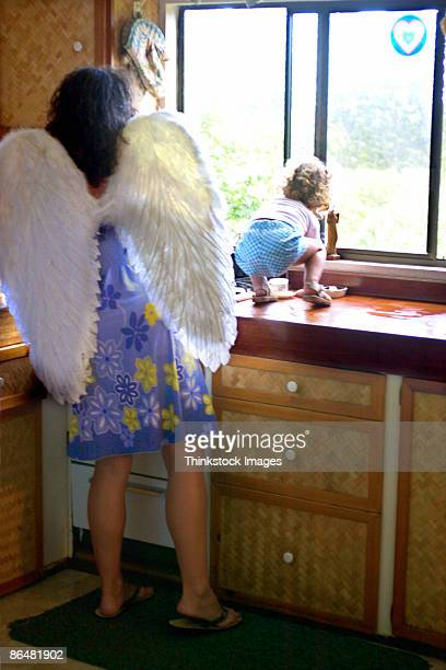 Mother with angel wings watching baby girl in kitchen