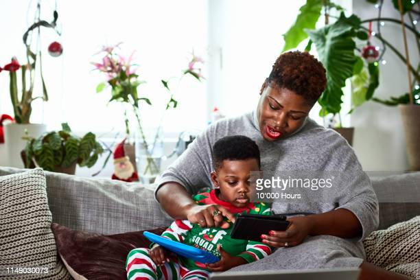 mother with arm around son using digital tablet - child stock pictures, royalty-free photos & images
