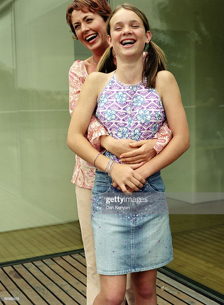 Mother with arms around daughter (12-14), laughing, outdoors : Stock Photo