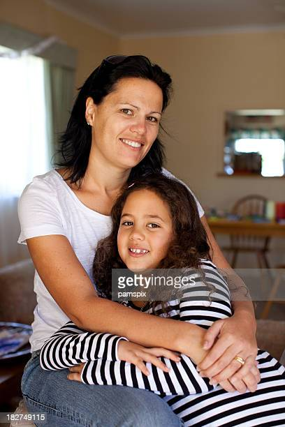 Mother with arms around her daughter indoors
