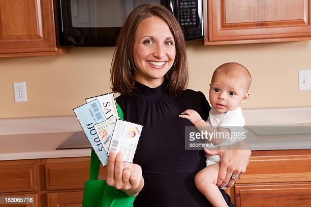 mother with baby and coupons - coupon stock photos and pictures