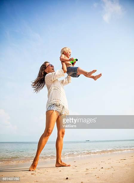 mère avec bébé sur plage tropicale - fesse enfant photos et images de collection