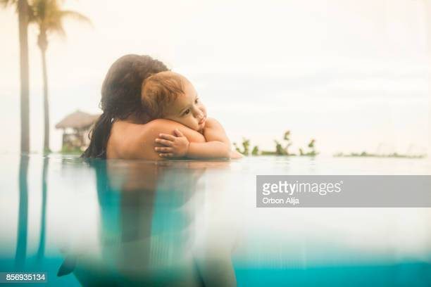 mother with baby boy in swimming pool - mexican and white baby stock photos and pictures