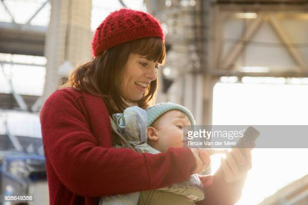 Mother with baby checks mobilephone at railway station.