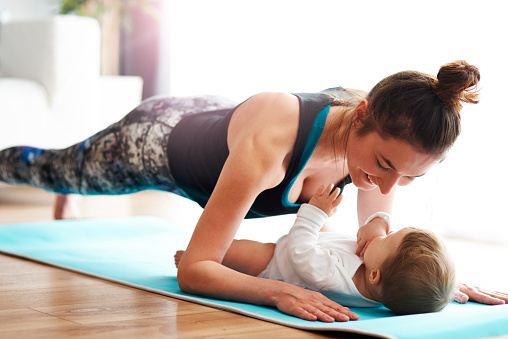 Mother with baby exercising on yoga mat at home - gettyimageskorea