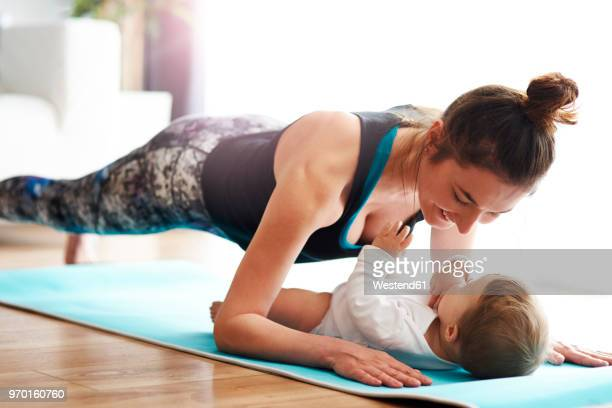 mother with baby exercising on yoga mat at home - baby human age stock pictures, royalty-free photos & images