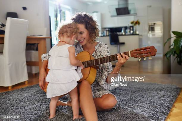 mother with baby girl playing guitar at home - linda oliver fotografías e imágenes de stock