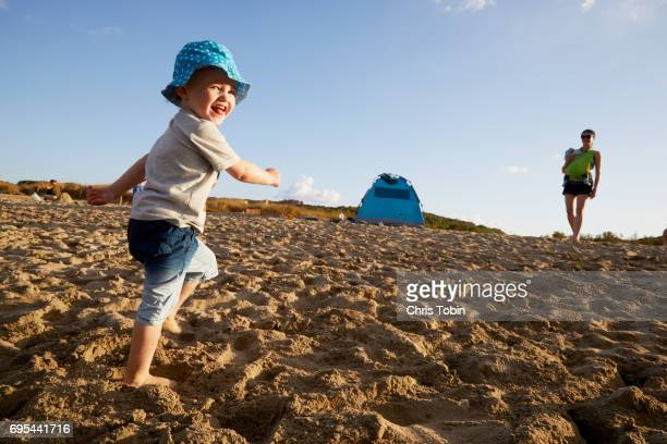 mother with baby in background watching toddler boy running on the beach - looking over shoulder stock pictures, royalty-free photos & images