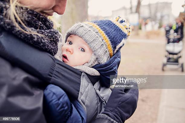 Mother with baby in carrier, outdoors in winter.