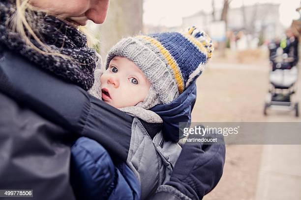 Mãe com bebê no suporte, ao ar livre no inverno.