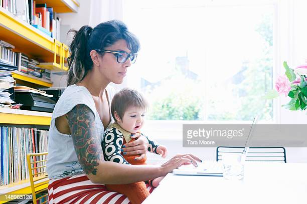 mother with baby in lap working on laptop at home - leanincollection stock pictures, royalty-free photos & images
