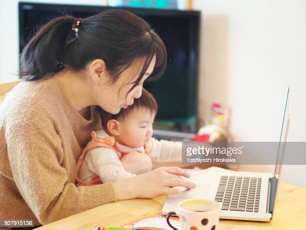 mother with baby in lap working on laptop at home - バーチャルオフィス ストックフォトと画像