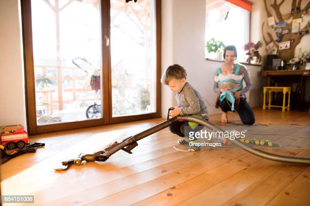 Mother with baby in sling, son helping to vacuum the floors