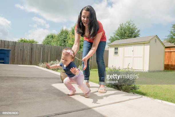 Mother with Baby Learning to Walk in Backyard USA