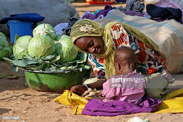 Mother with baby selling vegetables at market in the town Zinder, Niger, Western Africa.