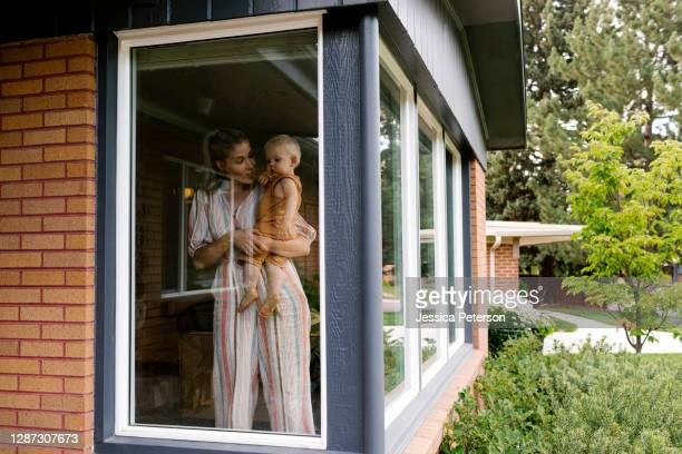 mother with baby son (18-23 months) standing behind window - 18 23 months stock pictures, royalty-free photos & images