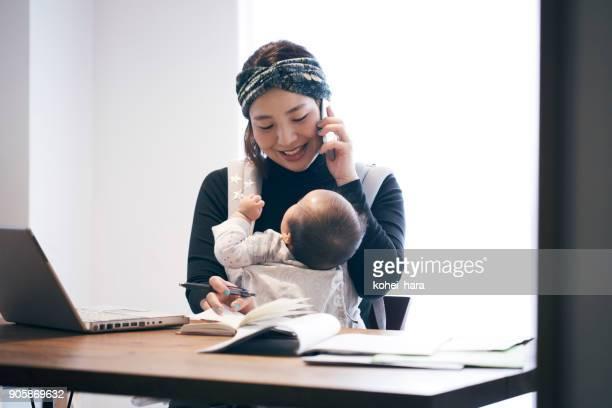 自宅で仕事の赤ちゃんと母親 - 警護する ストックフォトと画像