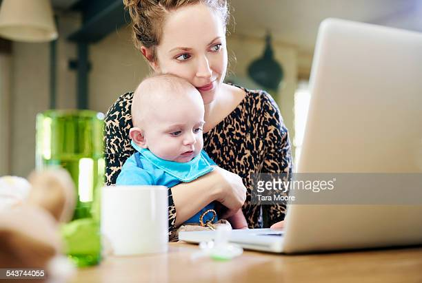 mother with baby working on laptop at home - computer equipment stock pictures, royalty-free photos & images