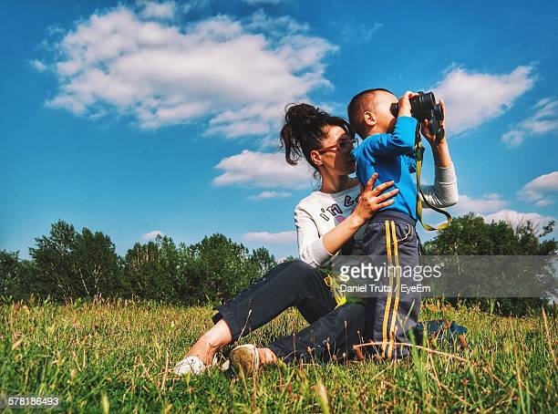 Mother With Boy Looking Through Binoculars At Park Against Sky