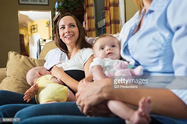 Madre con il neonato allattato al seno durante la riunione del gruppo di supporto in allattamento