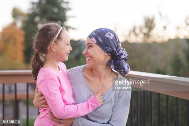 mother with cancer hugging daughter - cancer illness stock pictures, royalty-free photos & images