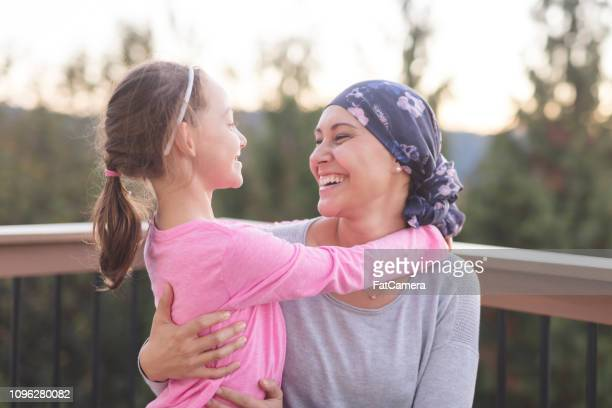 mother with cancer hugging her daughter - survival stock pictures, royalty-free photos & images