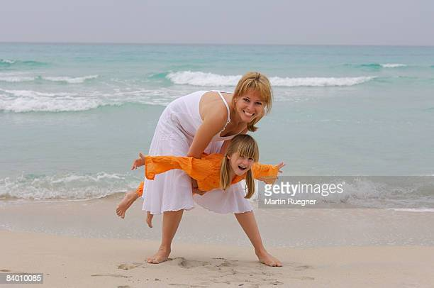 mother (25-30) with child (5 years) fun at beach. - 25 29 years stock pictures, royalty-free photos & images